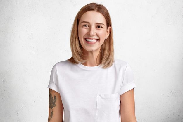 Adorável mulher caucasiana com expressão positiva, tem dentes brancos perfeitos, pele saudável, tatuagem no braço, cabelo curto alegra boas notícias