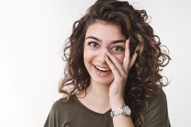 Adorável mulher caucasiana de cabelos cacheados se divertindo, rindo, segurando a palma da mão, espiando por entre os dedos, amigos mostram surpresa sorrindo antecipando ansioso, ver fundo branco em pé