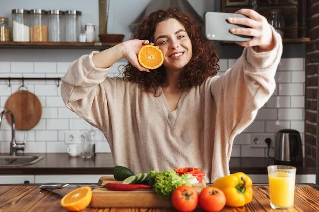 Adorável mulher caucasiana tirando foto de selfie no smartphone enquanto cozinha salada de legumes frescos no interior da cozinha em casa