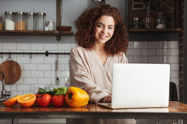 Adorável mulher caucasiana usando laptop enquanto cozinha salada de legumes fresca no interior da cozinha em casa