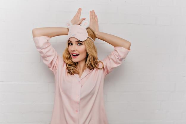 Adorável mulher com cabelo loiro curto se divertindo de pijama. retrato interior de uma linda garota em traje de noite rosa e máscara de dormir.