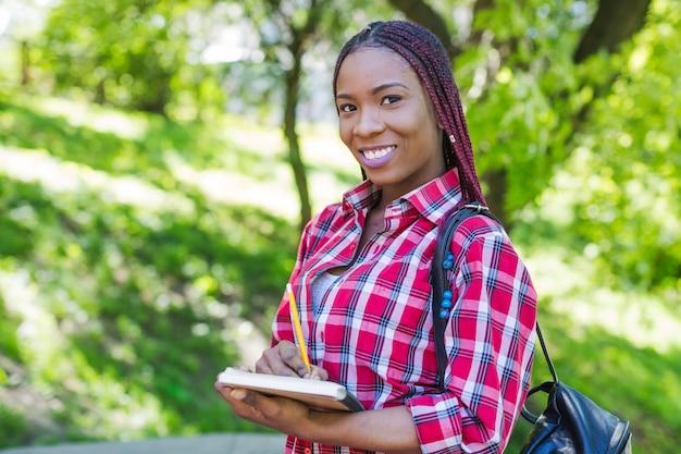 Adorável mulher com caderno no parque