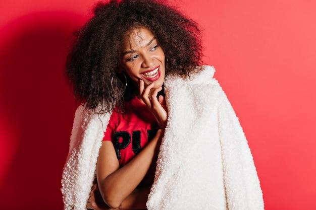 Adorável mulher com casaco posando com um sorriso feliz