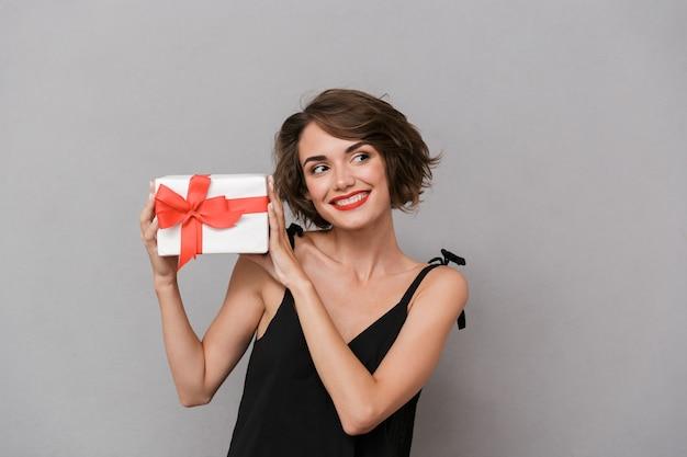 Adorável mulher com vestido preto segurando uma caixa de presente, isolada sobre uma parede cinza