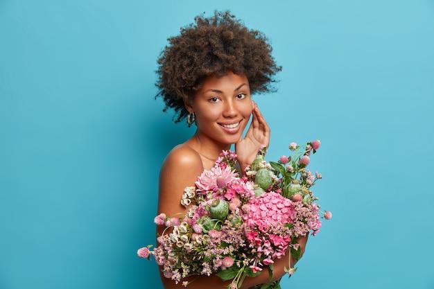 Adorável mulher de cabelo encaracolado em pé com ombros nus tocando o rosto delicadamente segurando um lindo buquê de flores e expressando emoções positivas