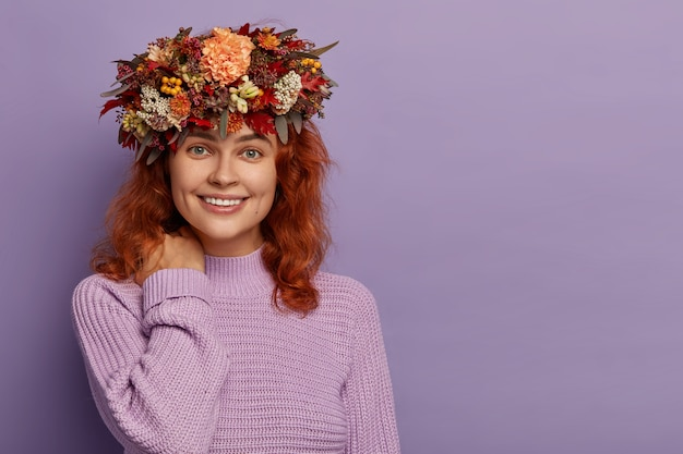 Adorável mulher de cabelos vermelhos tem um sorriso gentil, toca o pescoço, pele saudável, usa coroa de flores feita à mão, macacão roxo de malha, fica contra a parede violeta com espaço vazio.