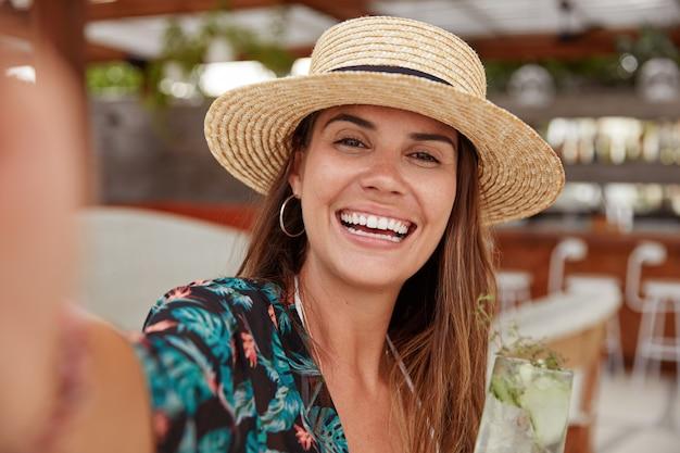 Adorável mulher de chapéu de palha, usa blusa, faz uma selfie.