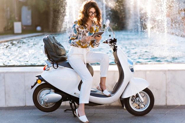 Adorável mulher de negócios sentada na scooter com um tablet nas mãos e sorrindo