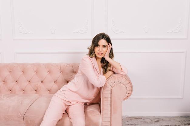 Adorável mulher de pijama sentada no sofá