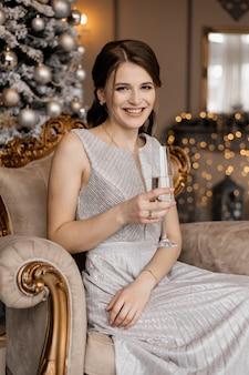 Adorável mulher de vestido prata senta-se diante de uma árvore de natal com uma taça de champanhe na mão