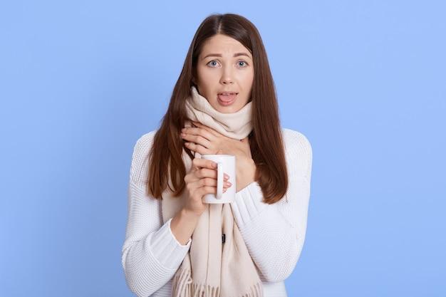 Adorável mulher doente bebendo bebida quente e mostrando a língua, mantendo a mão no pescoço enrolada em um lenço