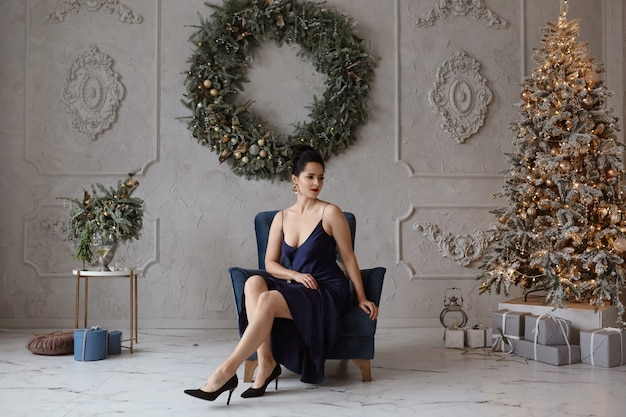 Adorável mulher em um elegante vestido azul escuro na frente da árvore de natal adorável modelo feminino na moda ...