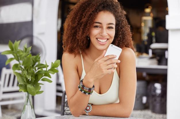 Adorável mulher encaracolada com expressão positiva segura o celular nas mãos, mensagens nas redes sociais, desfruta de conexão de internet de alta velocidade no refeitório.