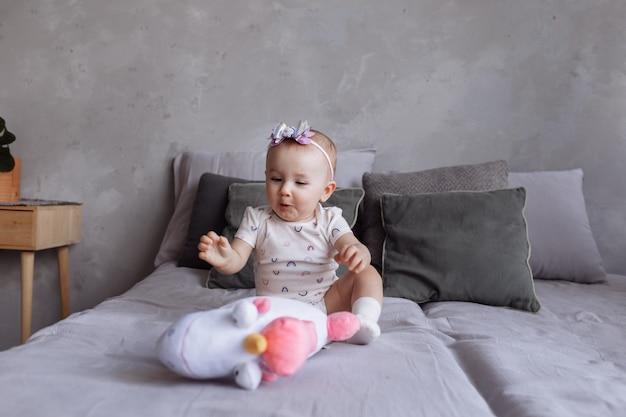 Adorável mulher está brincando com unicórnio de brinquedo na cama em casa. conceito de dia da infância. feliz dia da família