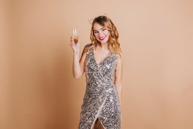 Adorável mulher europeia com lábios vermelhos, bebendo champanhe, comemorando o natal na festa