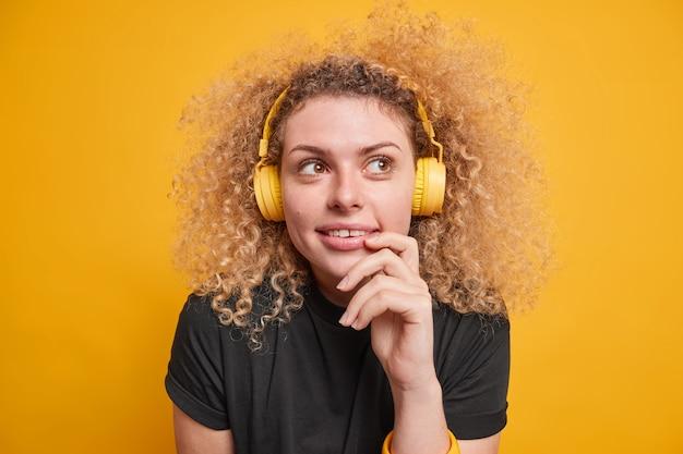 Adorável mulher européia milenar com expressão pensativa e sonhadora olhando para longe ouve música por meio de fones de ouvido sem fio vestida casualmente, estando imersa em pensamentos, poses contra uma parede amarela vívida