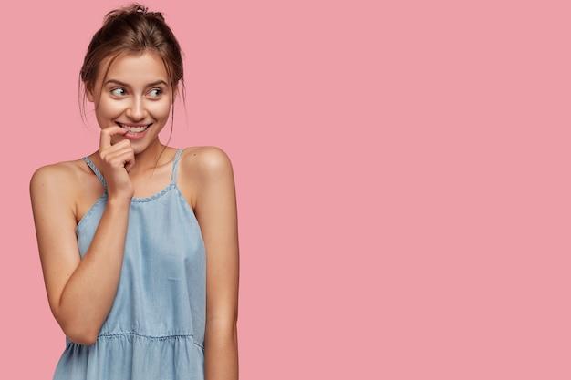 Adorável mulher europeia sorridente e feliz mantendo o dedo na boca