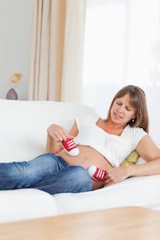 Adorável mulher grávida brincando com sapatos de bebê vermelhos enquanto deita no sofá