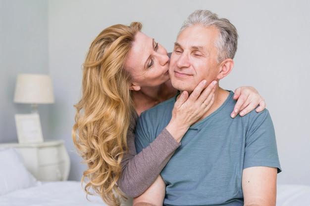 Adorável mulher idosa beijando seu marido