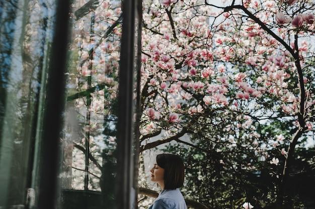 Adorável mulher jovem com cabelo curto fica sob a árvore de florescência rosa