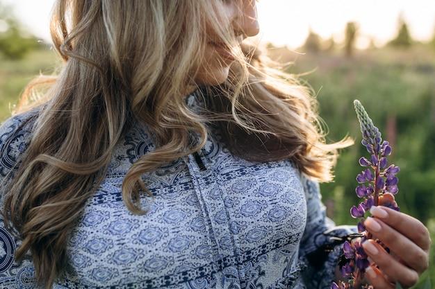 Adorável mulher loira de vestido azul atravessa o campo de flores de lavanda violeta
