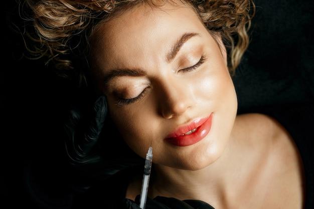 Adorável mulher loira tendo injeção de preenchimento no rosto. conceito de cosmetologia. vista do topo