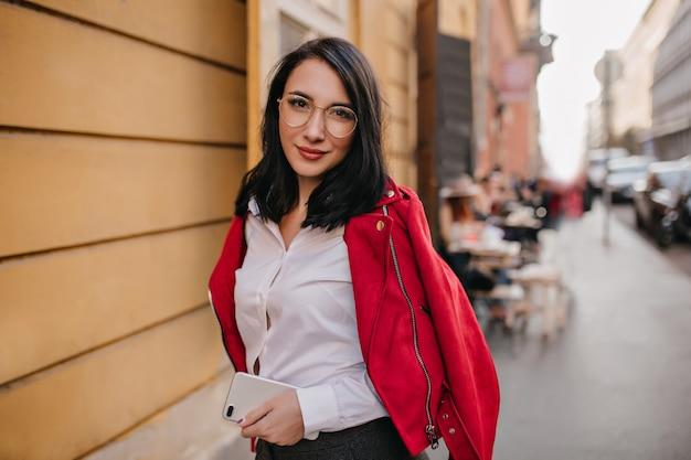 Adorável mulher morena com cabelo liso em pé com smartpone na parede da cidade e sorrindo