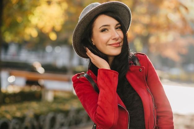 Adorável mulher morena com elegante chapéu cinza posando em desfocar a parede natural