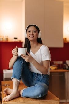 Adorável mulher morena com fones de ouvido, sentada na cozinha com uma xícara de chá