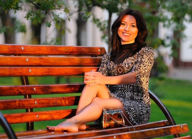 Adorável mulher morena europeia se senta em um banco de madeira no parque. menina de vestido e sapatos falando ao ar livre no celular