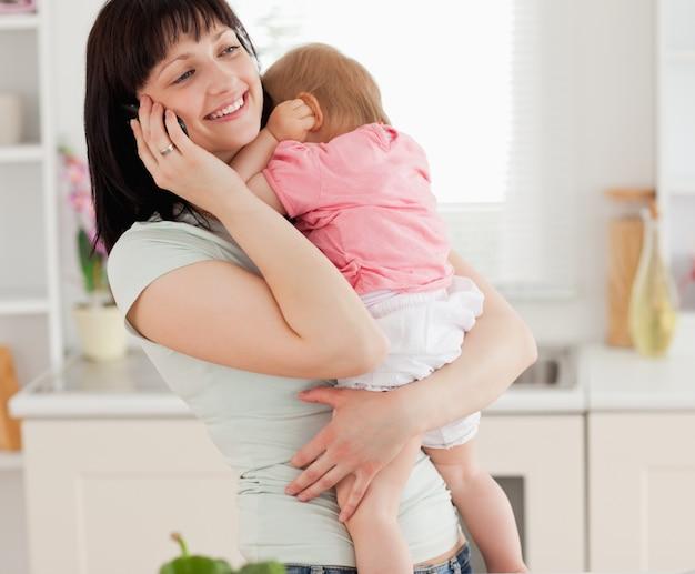 Adorável mulher morena no telefone enquanto segurava o bebê em seus braços