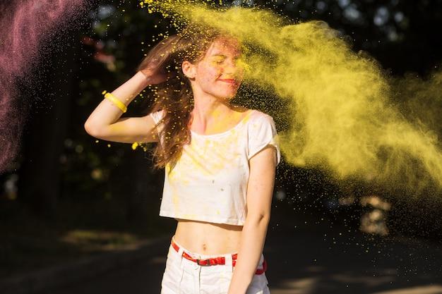 Adorável mulher morena posando em uma nuvem de tinta amarela seca holi no parque
