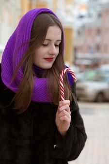 Adorável mulher morena segurando uma bengala de caramelo na rua