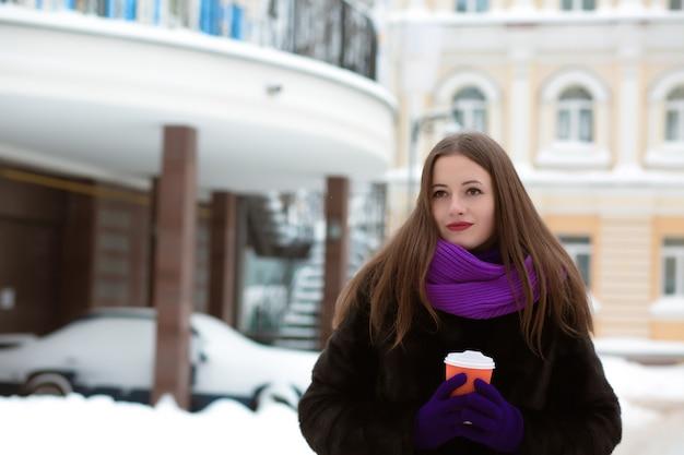 Adorável mulher morena vestida com roupas de inverno, posando na rua com uma xícara de café