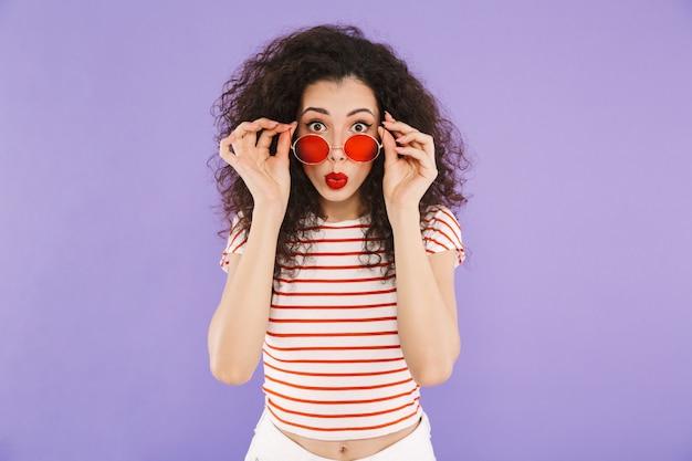 Adorável mulher na moda com cabelos cacheados no desgaste do verão e óculos de sol olhando para a frente