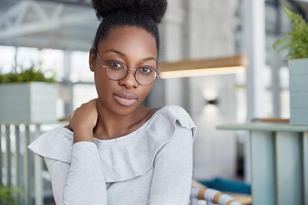 Adorável mulher séria de pele escura com expressão confiante, usa óculos, trabalha em relatório científico, poses interiores.