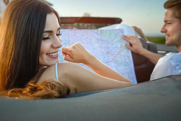 Adorável mulher sorrindo, homem segurando o mapa enquanto está sentado no cabriolet.