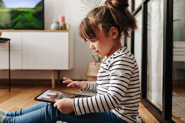 Adorável mulherzinha de bom humor assiste desenhos animados em tablet e poses na sala de estar.