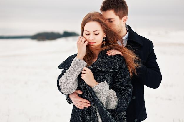 Adorável namorado que abraça sua amiga em um dia ventoso