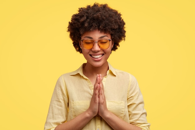 Adorável oração de mulher satisfeita mantém as mãos em gesto de oração, tem sorriso gentil, fecha os olhos e veste uma blusa estilosa