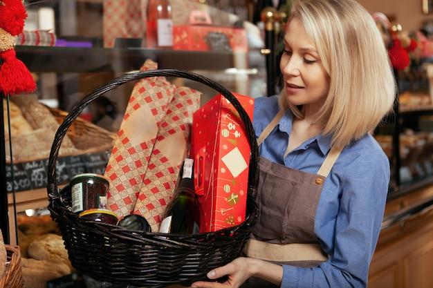 Adorável padeiro feminino segurando cesta com comida deliciosa, vendida em sua padaria.