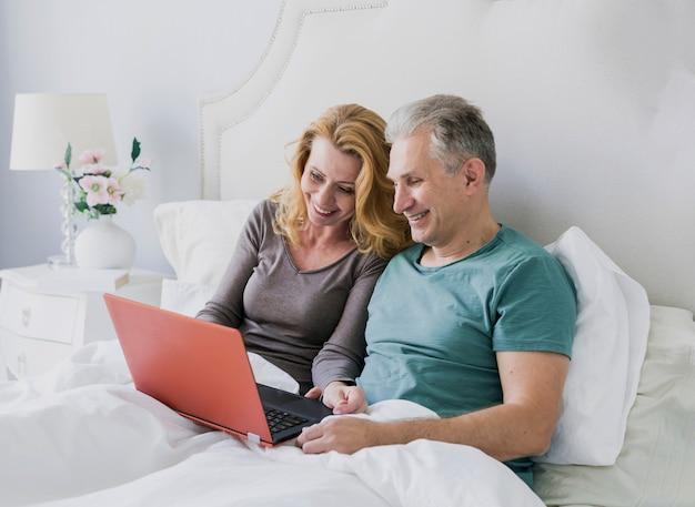 Adorável, par idoso, cama, com, laptop