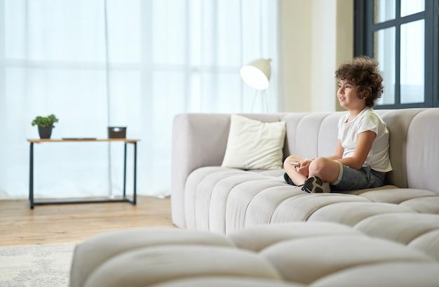 Adorável rapaz latino sentado num sofá com o smartphone a ver televisão enquanto passa o tempo