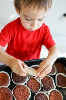 Adorável rapaz pequeno em casa saboreando cupcakes