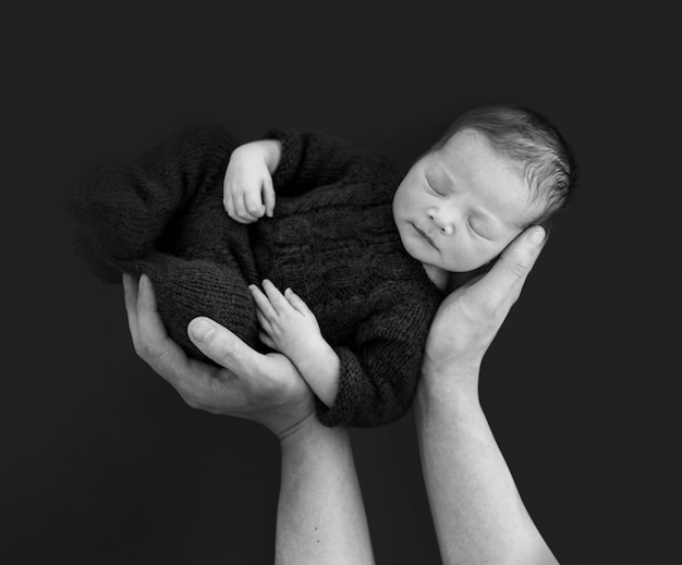 Adorável recém-nascido deitado nas mãos