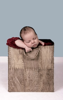 Adorável recém-nascido dormindo dentro de uma caixa de papelão