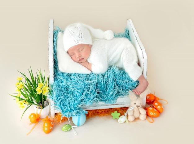 Adorável recém-nascido dormindo na cama pequena