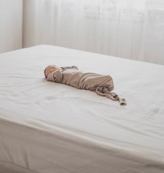 Adorável recém-nascido dormindo na cama