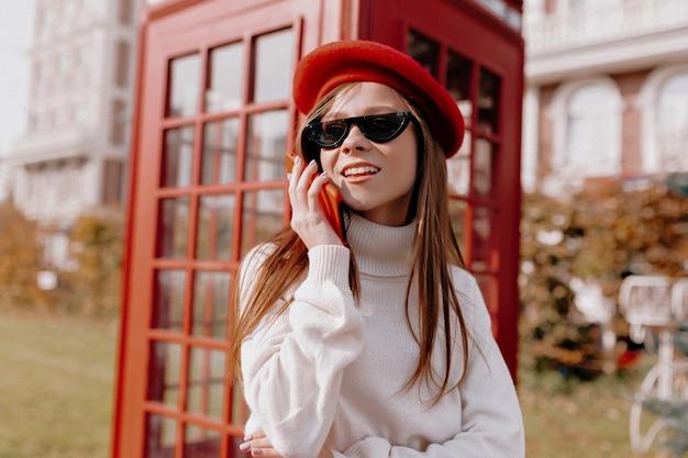 Adorável senhora com cabelo comprido, usando boné vermelho e óculos pretos, perto de uma cabine telefônica vermelha