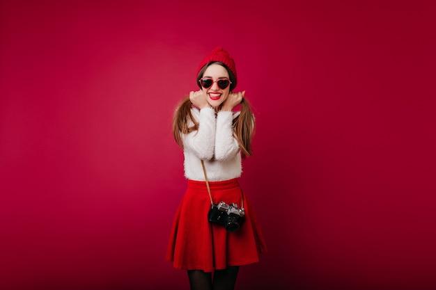 Adorável senhora de cabelos escuros expressando felicidade durante a sessão de fotos interna